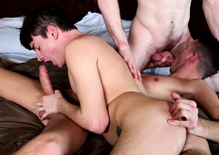 Three taking young boys fulfilling their sexual desires on the bed