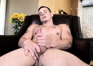 Tattooed jock Deeks abuses his bushwa with a hard wanking alongside the living room