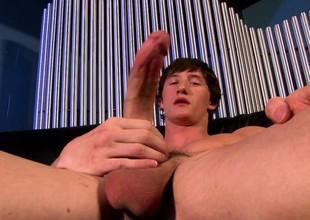 Sexy stud Lance Alexander sits on the couch and milks his long shaft