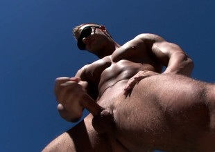 Attractive stud sensually brings his long dick to shinny up under the sun