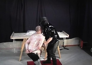 Sadistic dextrous wraps less his slave in cellophane as he makes him suck